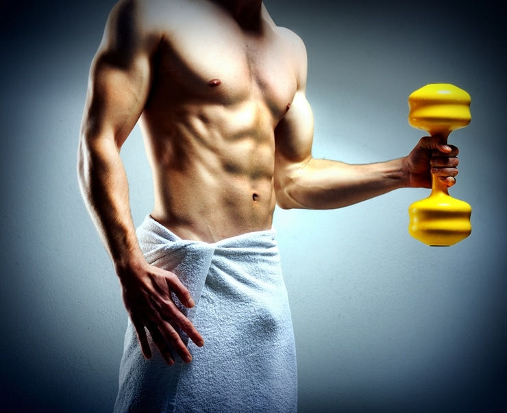 Modybuilder doing heavy weight exercise with dumbbells against d