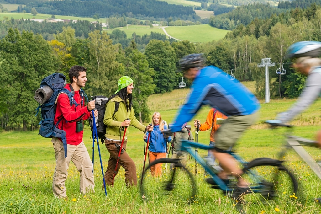 People hiking and riding bikes on summer vacation nature landscape